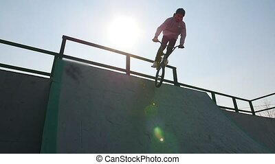 A professional BMX rider in grey hoodie riding down on the...