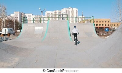 A professional BMX rider in grey hoodie riding on ramps in...