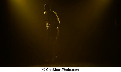 A professional breakdance dancer performs a difficult rotation on his arms. A man performs street dance in a dark studio with a yellow stage light. Close up