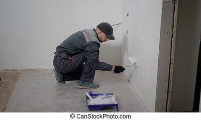 a professional builder in a working form uses paint and a...