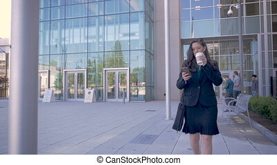 A professional business woman in her 30s walking using smartphone technology