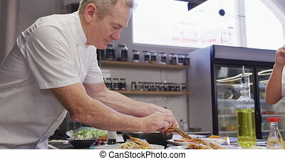 A professional Caucasian male chef wearing chefs whites in a restaurant kitchen, putting food on a plate in slow motion
