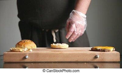 A professional chef prepares a cheeseburger with a big chop...