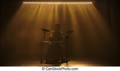A professional drumstick musician plays drums in the dark ...