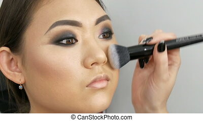 A professional make-up artist applies a concealer with special brush to Asian girl model face in visage studio close up view. High fashion, shooting video in studio