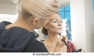 A professional make-up artist does the make-up of the model. Apply a special brush with a tonal paint. Preparation for an artistic photo shoot