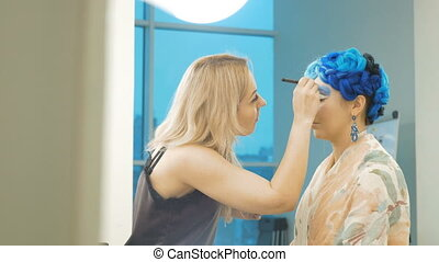 A professional make-up artist draws blue shadows on the eyelids of the model. Preparation for an artistic photo shoot