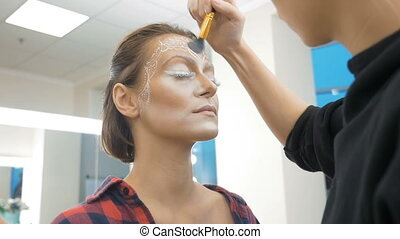 A professional make-up artist draws body art on the face of the model. Preparing for a beauty contest.
