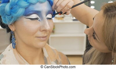 A professional make-up artist paints on the eyelids of the...