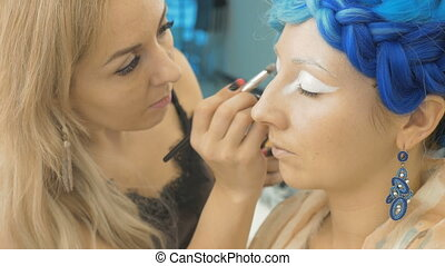A professional make-up artist paints on the eyelids of the model. Preparation for an artistic photo shoot
