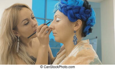 A professional make-up artist paints the eyes of the model. Preparation for an artistic photo shoot
