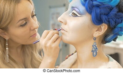 A professional make-up artist paints the model's lips. Creates a dream image. Preparation for an artistic photo shoot