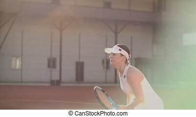 A professional woman in a white tight suit hits the ball...