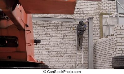 a professional worker in protective uniform is engaged in welding a building object, persons are on the background of a brick wall