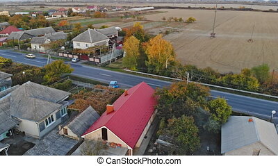 A profile moving aerial establishing shot of a typical small town at sunset.