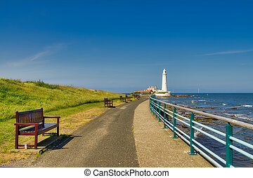 A promenade in Whitley bay with St Mary's lighthouse in the background.
