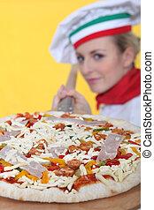 A proud pizza maker