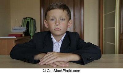 A pupil in school uniform sits at a desk - Boy schoolchild...