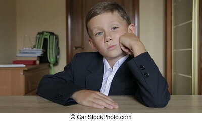 A pupil in school uniform sits at a desk