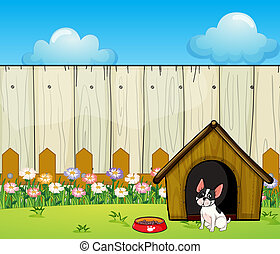 A puppy in front of the doghouse inside the fence