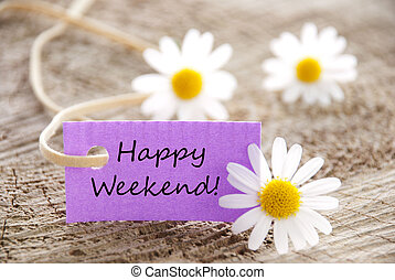 A Purple Label with Happy Weekend on it and white Flowers in the Background