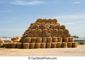 pyramid of hay with the blue cloudy sky in the background
