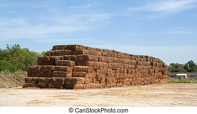 pyramid of hay with the blue cloudy sky
