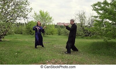 Qigong master and his disciple practice tai Chi in nature in a Park