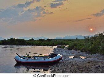 A raft moored on a sandy beach under a midnight sun.