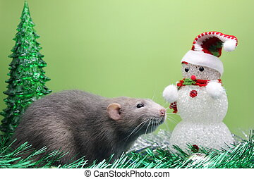 A rat is a symbol of the new year 2020 near a toy Christmas tree and a snowman among tinsel.