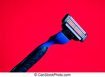 A razor with a new blade on a red background.