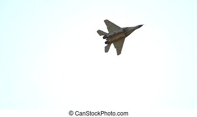 A reactive plane flying in the sky and performing a show in the white bright sky