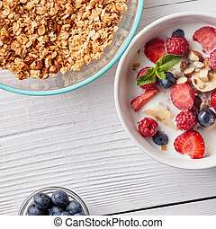 A ready breakfast of natural organic ingredients - granola, berries, nuts, honey, milk for the preparation of natural healthy food on white table.