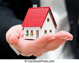 A real estate agent holding a small new house in her hands. ...