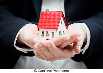 A real estate agent holding a small new house in her hands