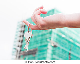 A real estate agent holding keys to a new apartment in her...