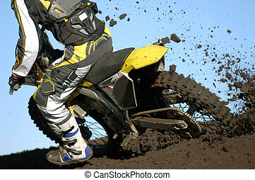 A rear view of a motocross rider races through the dirt and mud during a race.
