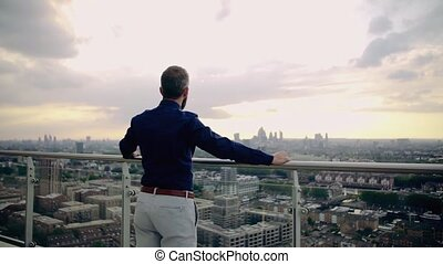 A rear view of businessman standing against London view...
