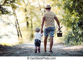 A rear view of father with a small toddler son going fishing.