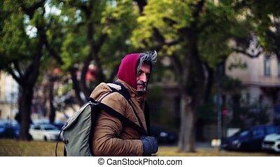 A rear view of homeless beggar man walking outdoors in city,...