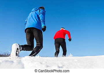 A rear view of senior couple jogging in snowy winter nature.