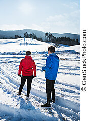 A rear view of senior couple runners standing in winter nature, resting.
