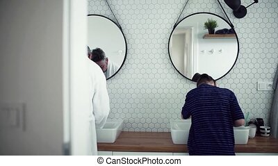 A rear view of small son with father washing in the bathroom...