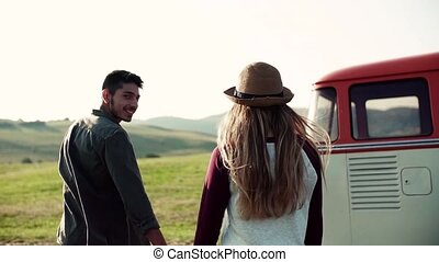 A rear view of young couple on a roadtrip through...