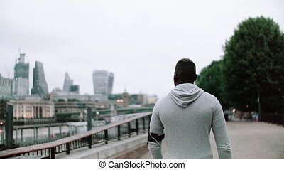 A rear view of young sporty black man runner with smart phone walking on the bridge in a city.