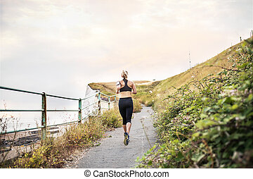 A rear view of young sporty woman runner running by sea in nature.