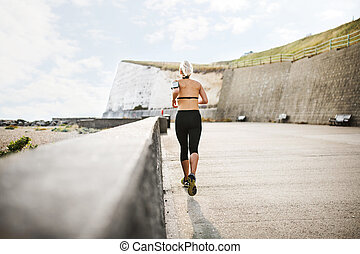 A rear view of young sporty woman runner running outside on a beach in nature.