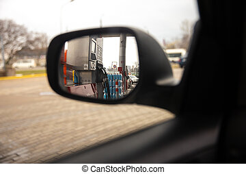 A rear window in a side car mirror during a break stop at a gas station