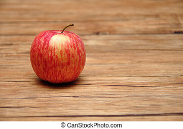 A red apple on a wooden background