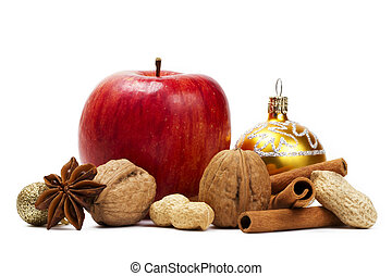 a red apple, star anise, walnuts and peanuts, a christmas ball and cinnamon sticks on white background